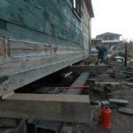 Мы поднимаем деревянный дом на домкратах для ремонта.